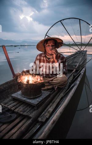 Inle lake, Nyaungshwe township, Taunggyi district, Myanmar (Burma). Local fisherman before dawn with fireplace on - Stock Photo