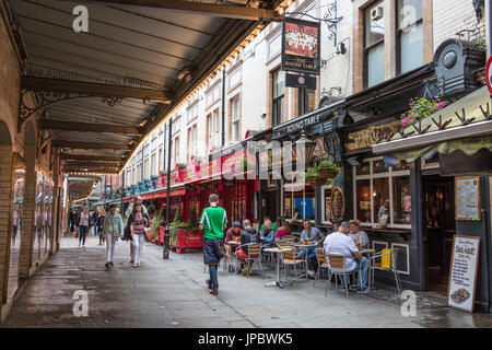 People walk in the pedestrian area with cafe and restaurants of Leicester Square Covent Garden Camden London United - Stock Photo