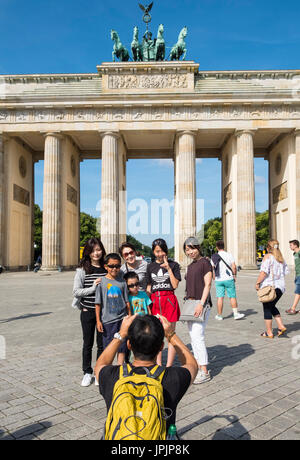 Asian tour group posting for photograph in front of Brandenburg Gate in Mitte district of Berlin Germany - Stock Photo