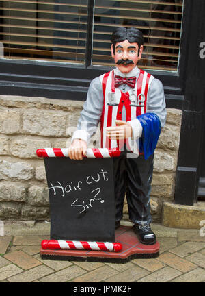 Unique, colourful, and humorous sign on footpath outside barber's shop with statue of old fashioned barber asking - Stock Photo