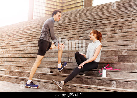 Active young couple resting after workout outdoors - Stock Photo