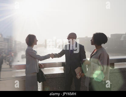 Silhouette business people handshaking on sunny urban bridge over Thames River, London, UK - Stock Photo