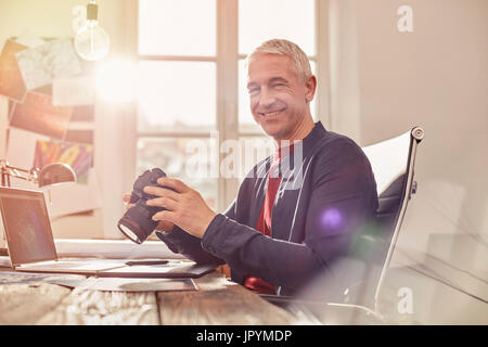 Portrait smiling, confident male photographer with digital camera working at laptop in sunny office - Stock Photo