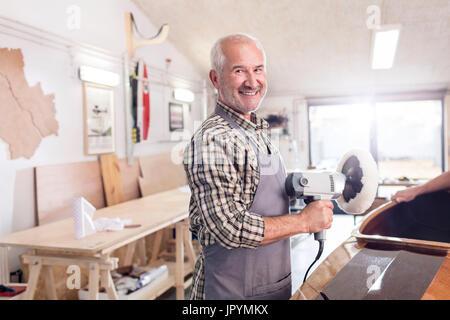 Portrait smiling, confident senior male carpenter using a buffer sander on wood boat in workshop - Stock Photo