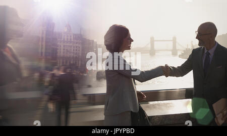 Silhouette business people handshaking on sunny bridge over River Thames, London, UK - Stock Photo