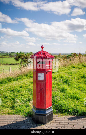 Red post box with summer sky in the background located at the Giant`s Causeway Bushmills Antrim Northern Ireland - Stock Photo