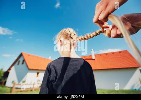 Young woman making hair braids of the little girl on the garden in the countryside. - Stock Photo