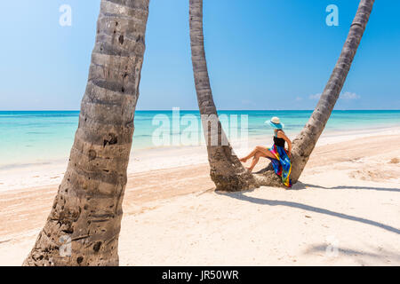 Juanillo Beach (playa Juanillo), Punta Cana, Dominican Republic. Woman under high palm trees on the beach. - Stock Photo