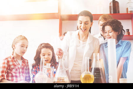 Group of four pupils standing around their teacher - Stock Photo