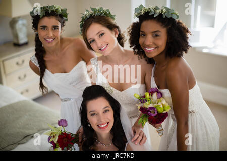 Portrait of smiling bride and bridesmaid in living room at home - Stock Photo