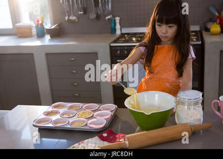 Girl mixing batter in bowl at kitchen counter - Stock Photo