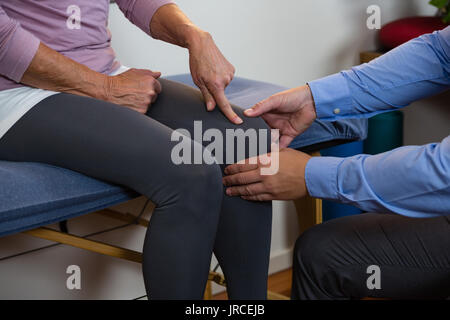 Physiotherapist examining a female patients knee in clinic - Stock Photo