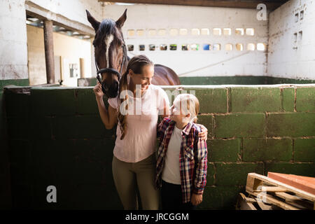 Sisters talking while standing by horse in stable - Stock Photo