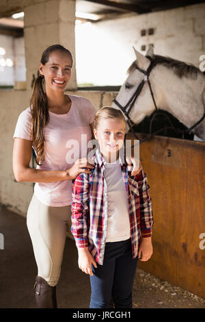 Portrait of sisters standing by horse in stable - Stock Photo