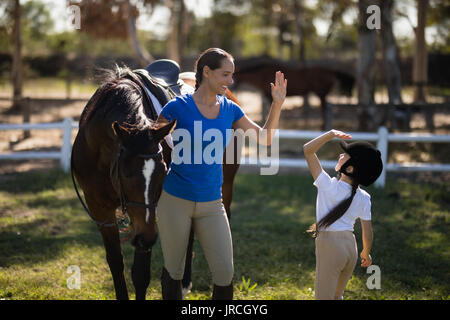 Sisters giving high five while standing by horse at paddock - Stock Photo