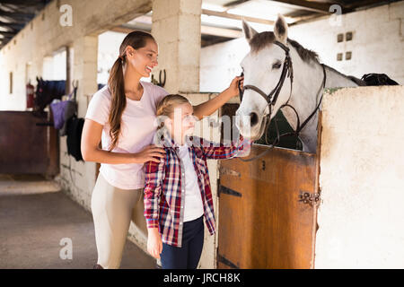 Smiling sisters stroking horse while standing in stable - Stock Photo