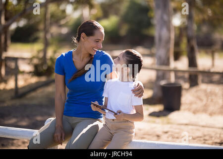 Smiling sisters talking while sitting on railing at paddock - Stock Photo