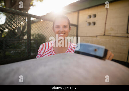 Portrait of smiling female jockey cleaning horse at barn - Stock Photo