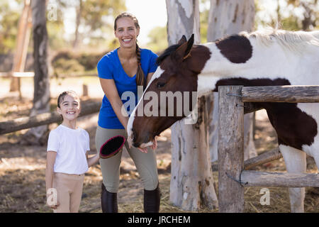 Portrait of smiling sister with horse while standing at paddock - Stock Photo