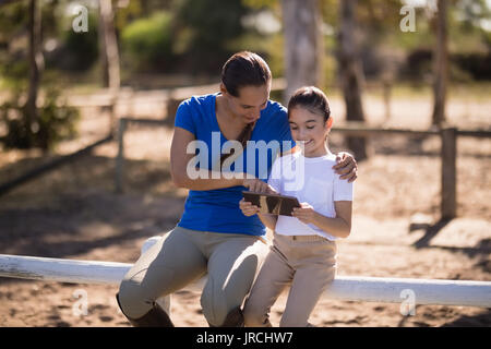 Smiling sisters using tablet computer while sitting on railing at paddock - Stock Photo
