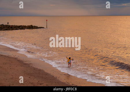 Sidmouth, Devon, UK. 4th Aug 2017. UK Weather. A woman enjoys a paddle in the sea as the sun goes down in Sidmouth. - Stock Photo