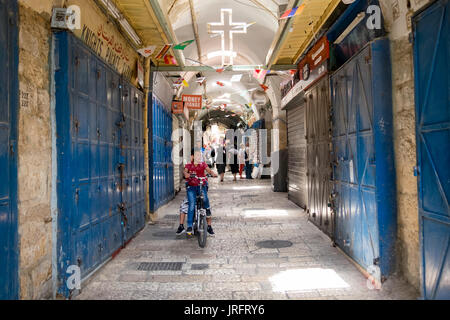 Arab children playing in the arcades of the Christian Quarter of the Old City of Jerusalem during a closure of shops - Stock Photo