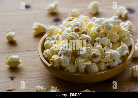 fresh salted popcorn in bowl on wooden table - Stock Photo