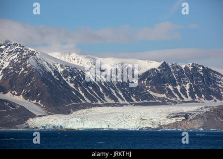Kronebreen or Crown glacier and snow covered mountains, Kongsfjord. Taken in June, Spitsbergen, Svalbard, Norway - Stock Photo