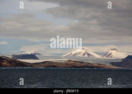 Kronebreen or Crown glacier, Kongsfjord and snow covered, pyramidal shaped mountains. Taken in June, Spitsbergen, - Stock Photo