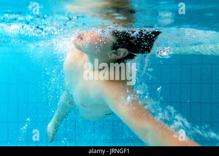 A boy diving and swimming in a swimmingpool, underwater photos. - Stock Photo