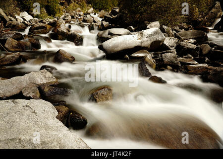 Fast flowing river stream of water coming down from the mountains passing by big rocks on the riverbed. - Stock Photo