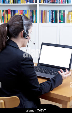 Rear view of a woman in a black blazer in front of her laptop with an empty screen, talking to someone, live or - Stock Photo