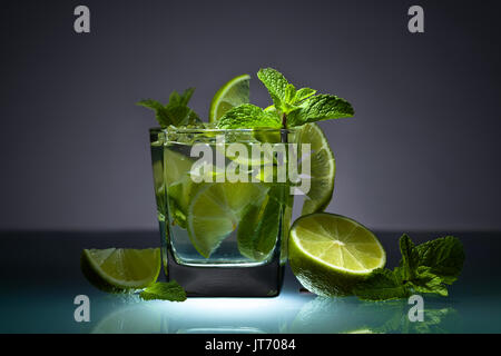 Cocktail with lime , ice  and peppermint leaves on a glass table in bar. - Stock Photo