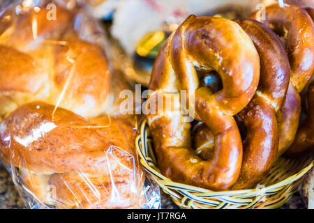 Closeup of fresh baked pretzels and challah bread in bakery baskets - Stock Photo