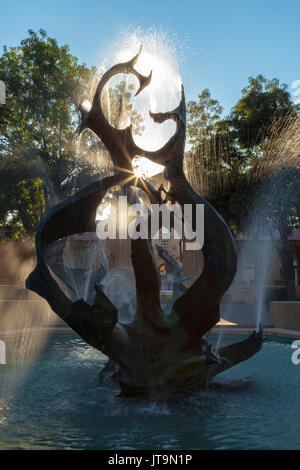 the metal artwork of water fountain with the backlit sun in Stanford University, Palo Alto,California. - Stock Photo