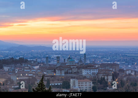 View of the medieval old town called Citta Alta on hilltop framed by the fiery orange sky at dawn, Bergamo, Lombardy, - Stock Photo