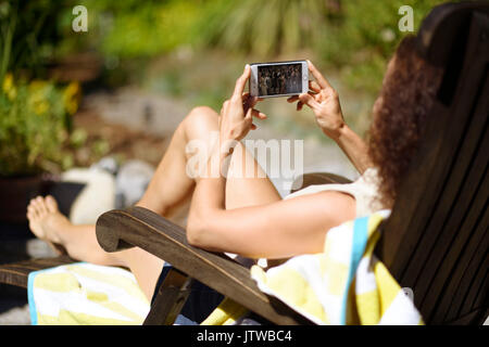 Young woman lying in a lounge chair in the sun, sunbathing with an iPhone in her hands, watching a movie on the - Stock Photo