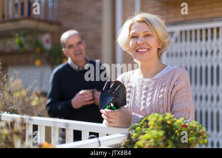 Smiling mature woman with horticultural sundry and aged man drinking tea in patio - Stock Photo