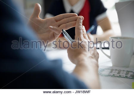 Close up male architect gesturing, discussing blueprints in meeting - Stock Photo