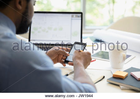 Male architect with cell phone drafting digital blueprint at laptop in office - Stock Photo