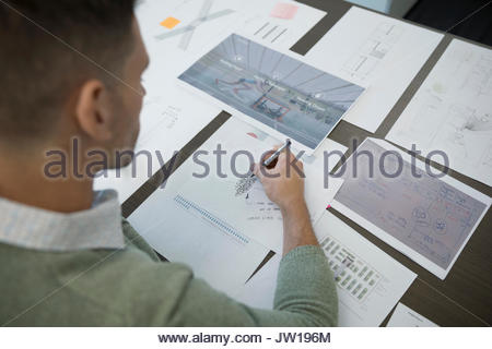 Male architect reviewing blueprints and proofs - Stock Photo