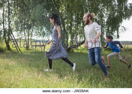 Playful family running in rural yard - Stock Photo