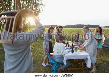 Friends setting the table and carrying chair for garden party dinner in rural summer yard - Stock Photo