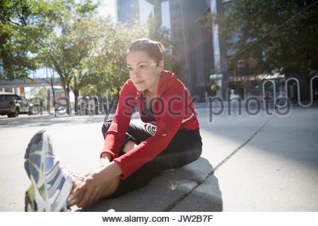 Woman stretching leg on sunny urban sidewalk - Stock Photo