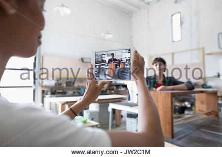 Female carpenter with digital tablet camera photographing coworker with wood bench in workshop - Stock Photo