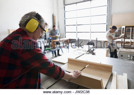 Male carpenter with ear protectors cutting wood at table saw in workshop - Stock Photo
