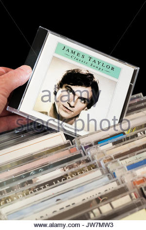 Classic Songs, James Taylor CD being chosen from among rows of other CD's, Dorset, England - Stock Photo
