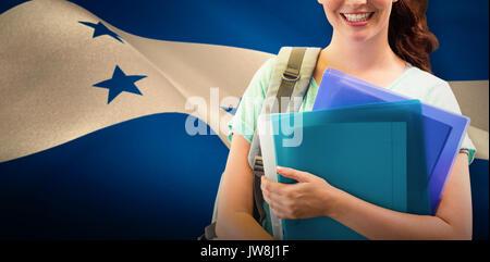 Smiling student against digitally generated honduran national flag - Stock Photo