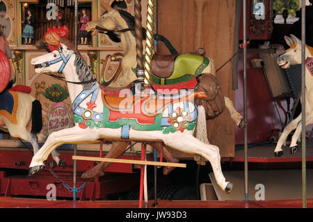 a fairground carousel ride-on horse decorated in brightly coloured paints and held on a golden spiral spindle. antique - Stock Photo