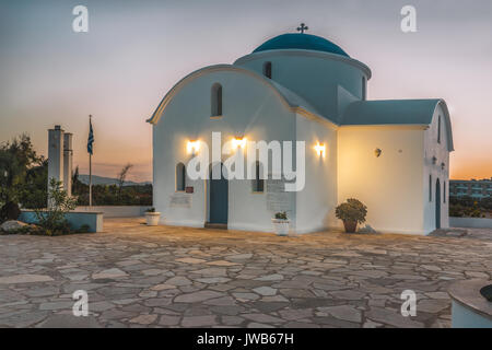A small white church on the beach in Paphos, Cyprus during the dawn. The sun rises above the horizon and illuminates - Stock Photo